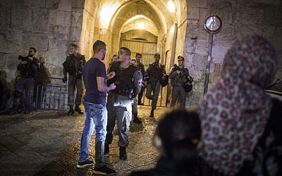 Palestinians wait outside Herod's Gate as security forces shut down the Old City of Jerusalem while searching for a suspect after a stabbing attack, on May 2, 2016. A Jewish man was stabbed and severely wounded (Hadas Parush/Flash90)