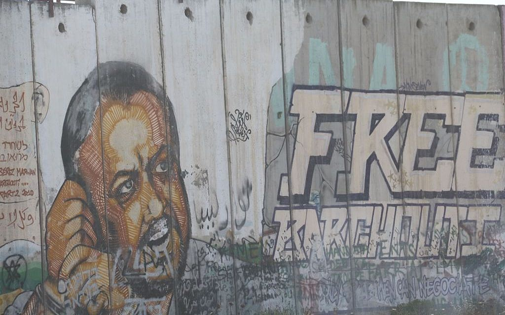 An image of Marwan Barghouti is seen painted on the security fence near the West Bank village of Qalandiya on May 6, 2016. (Photo by Haytham Shtayeh/Flash90)