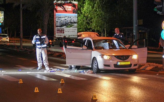 A forensic team examines the scene where Shai Shirazi, 30 was shot dead and another person wounded after a gunman opened fire on their car in Tel Aviv, May 7, 2016. (Moti Karelitz/Flash90)