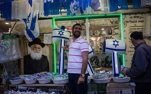 A man standing outside a shop that sells items for Israel's upcoming 68th Independence Day in the southern city of Ashkelon, May 8, 2016. (Corinna Kern/Flash90)