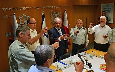 Benjamin Netanyahu, center, at a pre-holiday toast for top defense brass, including Maj. Gen. Yair Golan, far left, Defense Minister Moshe Ya'alon, left,  IDF Chief of Staff Lt. Gen. Gadi Eisenkot, right and Director General of the Defense Ministry Dan Harel, in army headquarters in Tel Aviv on May 9, 2016. (Kobi Gideon/GPO)