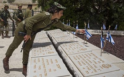 Israeli soldiers at Jerusalem's Mount of Olives military cemetery on May 10, 2016 place flags on the graves during a ceremony ahead of Memorial Day (Nati Shohat/Flash90)