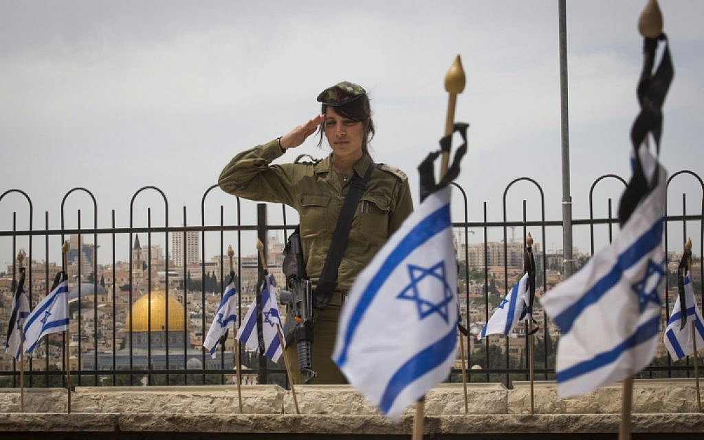 Israeli soldiers salute graves of fallen Israeli soldiers at the Mount of Olives cemetery after placing flags on the graves during a ceremony in preparation for Memorial Day, beginning tonight. May 10, 2016. (Nati Shohat/Flash90)