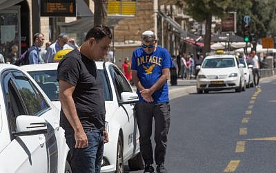 People stand still as a two-minute siren sounds across Israel, marking Memorial Day which commemorates the fallen Israeli soldiers in Jerusalem on May 11, 2016. (Nati Shohat/Flash90)