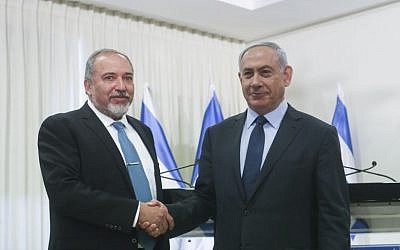 Prime Minister Benjamin Netanyahu (right) and Yisrael Beytenu party leader Avigdor Liberman shake hands after signing a coalition agreement in the Knesset on Wednesday, May 25, 2016 (Yonatan Sindel/Flash90)