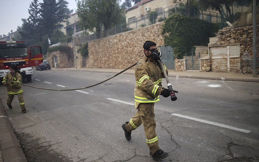 Illustrative: A firefighter works to put out a fire near the Jerusalem neighborhood of Ramot, on May 26, 2016. (Yonatan Sindel/Flash90)