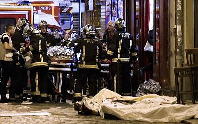 In this Friday, Nov. 13, 2015 file photo, rescue workers tend to victims of a jihadi terror attack in the 10th district of Paris. (AP Photo/Jacques Brinon, file)