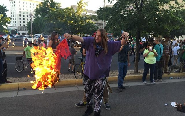 A protester holds a burning T-shirt as hundreds of people protest outside a rally for Republican presidential candidate Donald Trump in Albuquerque, New Mexico, May 24, 2016. (AP Photo/Russell Contreras)