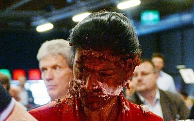 Germany's main opposition leader Sahra Wgenknecht has her face covered with cream after activists threw a cake at her during a party congress in Magdeburg, Germany, Saturday, May 28, 2016. (Hendrik Schmidt/dpa via AP)