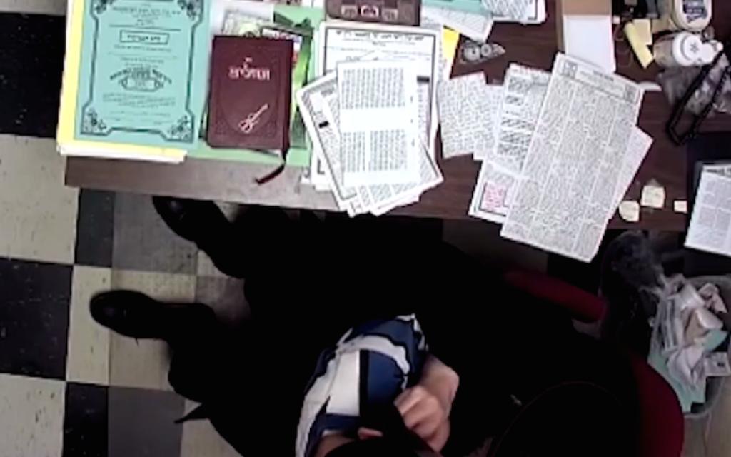 A screenshot from an 11-minute video showing a Hasidic principal handling a young boy. (Screenshot from YouTube)