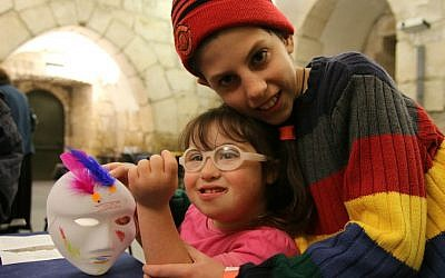 A brother hugs his sister at Tower of David Museum's Purim program for families with children with special needs, March 2016 (Ricky Rachman)