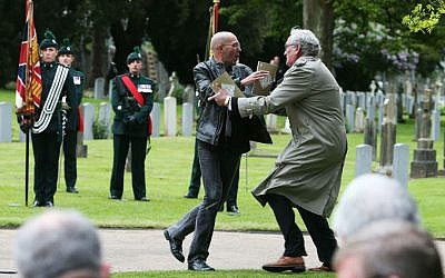 Canadian Ambassador to Ireland Kevin Vickers, right, wrestles with a protester during a state ceremony to remember the British soldiers who died during the Easter Rising at Grangegorman Military Cemetery, Dublin, Thursday May 26, 2016. (Brian Lawless/PA via AP)