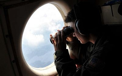 US Navy Lt. JG Dylon Porlas uses binoculars to look through the window of a US Navy Lockheed P-3C Orion patrol aircraft from Sigonella, Sicily on May 22, 2016, as part of the search for EgyptAir flight 804 that went missing on May 19. (AP Photo/Salvatore Cavalli)