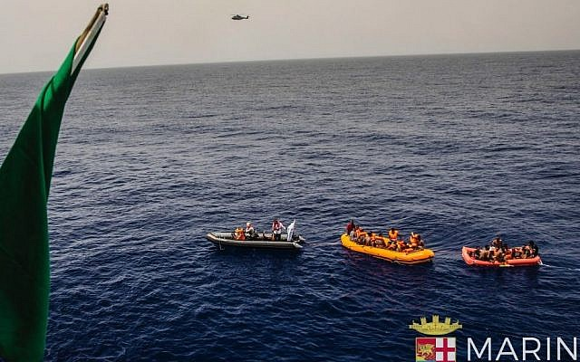 In this photo taken in the Mediterranean Sea, off the Libyan coast, Friday, May 27, 2016, rescuers tow migrants to the Italian Navy ship Vega, after the boat they were aboard sunk. (Raffaele Martino/Marina Militare via AP Photo)