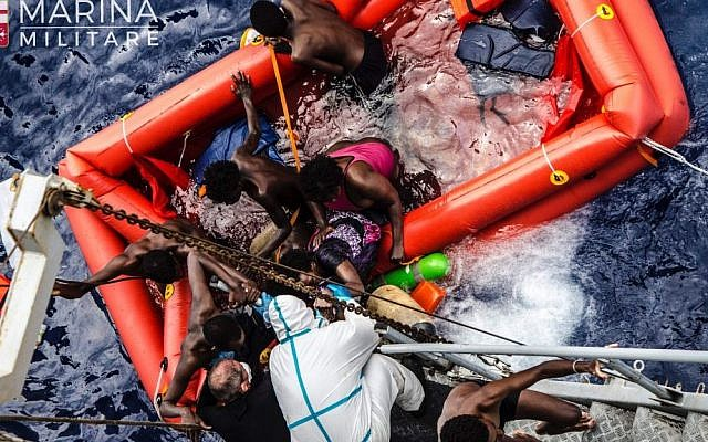 In this photo taken in the Mediterranean Sea, off the Libyan coast, Friday, May 27, 2016 rescuers help migrants to board the Italian Navy ship Vega, after the boat they were aboard sunk.(Raffaele Martino/Marina Militare via AP Photo)