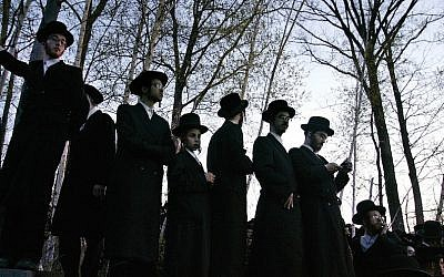 Illustrative: Hasidic Jews trying to see the burial of Rabbi Moses Teitelbaum in the upstate New York village of Kiryas Joel, April 25, 2006. (Stephen Chernin/Getty Images via JTA)