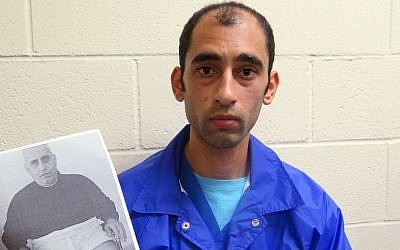 Mounis Hammouda, in an immigration detention center in Eloy, Arizona, on December 10, 2015, holds a photo of his father who, he claims, was tortured by Hamas. (AP/Astrid Galvan)