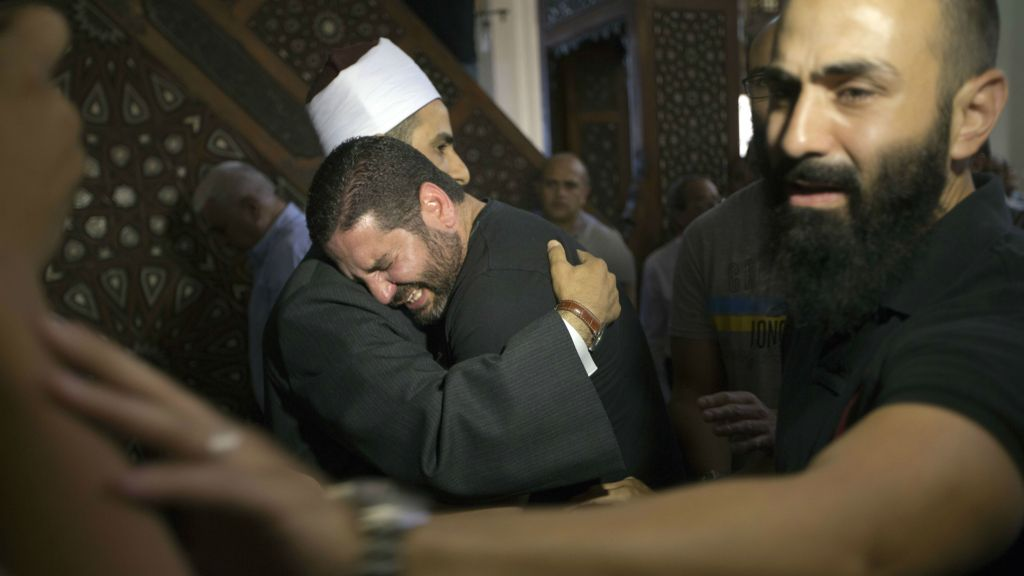 The Imam of Cairo's al Thawrah Mosque, Samir Abdel Bary, consoles Tarek Abu Laban, center, who lost four relatives in Thursday's EgyptAir plane crash, at a prayer gathering for the dead at al Thawrah Mosque, Friday, May 20, 2016. (AP Photo/Amr Nabil)