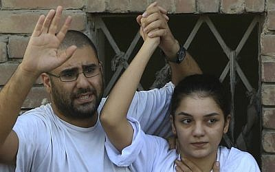 In this Thursday, Aug. 28, 2014 file photo prominent Egyptian blogger Alaa Abdel-Fattah, left, with his sister Sanaa Abdel-Fattah, speaks to the crowd after attending their father's funeral in Cairo, Egypt. (AP Photo/Hassan Ammar, File)