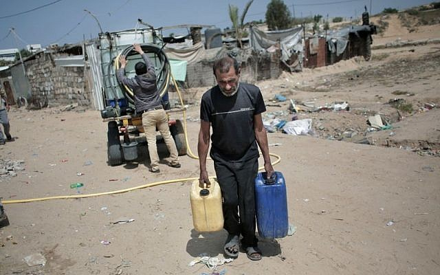 In this Saturday, April 16, 2016 photo, A Palestinian man carries plastic gallons he filled with drinking water from a vendor, background, in Khan Younis refugee camp, southern Gaza Strip. (AP Photo/Khalil Hamra)
