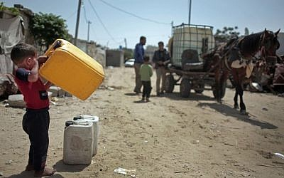 A Palestinian boy waits to fill plastic gallons with drinking water from a vendor in Khan Younis refugee camp, southern Gaza Strip, April 16, 2016. (AP Photo/Khalil Hamra)