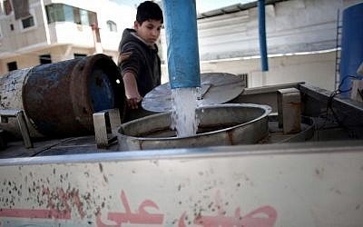 A Palestinian man fills tankers with drinking water for sale at a drinking water station in Gaza City, April 14, 2016. (AP Photo/Khalil Hamra)