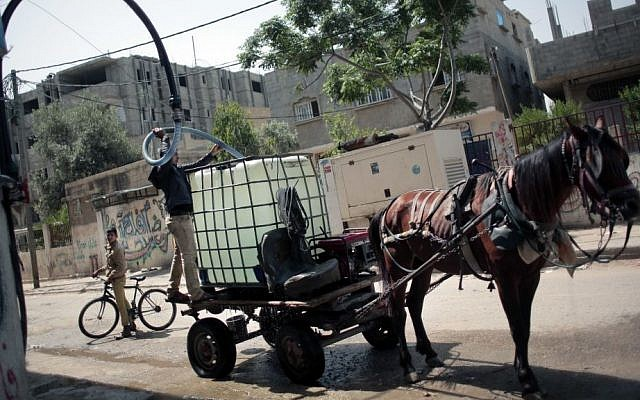 In this Saturday, April 16, 2016 photo, A Palestinian man fills a water tank on his horse cart with drinking water for sale from a water station in the Khan Younis refugee camp, southern Gaza Strip. (AP Photo/Khalil Hamra)