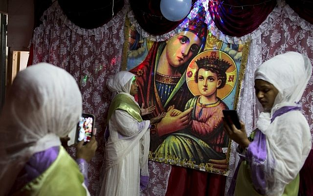 In this Saturday, May 7, 2016 photo, Members of the Eritrean Christian Orthodox migrants community take photos at a makeshift church in Tel Aviv, Israel. (AP Photo/Oded Balilty)