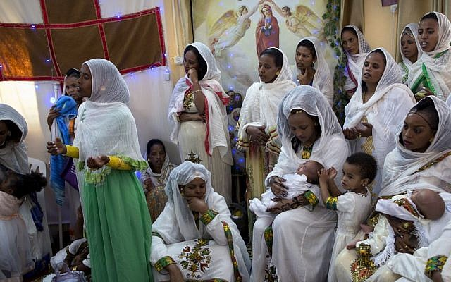 In this Saturday, April 23, 2016 photo, Eritrean Christian Orthodox migrant women hold their babies during a baptism ceremony at a makeshift church in Tel Aviv, Israel. (AP Photo/Oded Balilty)