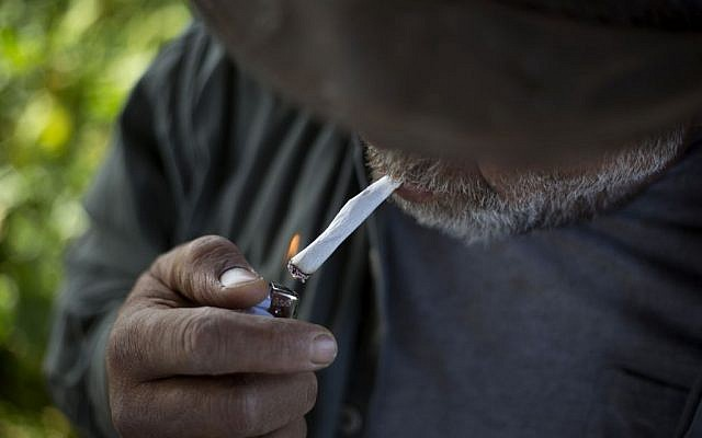 In this Thursday, April 21, 2016 photo, Druze cowboy Wafiq Ajami, smokes a cigarette after rounding up some 650 head of cattle in the Golan Heights near the border with Syria. (AP Photo/Ariel Schalit)