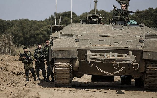 Israeli soldiers stand by an armored personnel carrier near the Israel Gaza border, Wednesday, May 4, 2016. (AP photo/Tsafrir Abayov)
