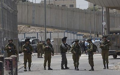 Israeli army soldiers secure the main entrance of the Qalandiya checkpoint, a main crossing point between Jerusalem and the West Bank city of Ramallah, April 27, 2016. (AP/Nasser Nasser)