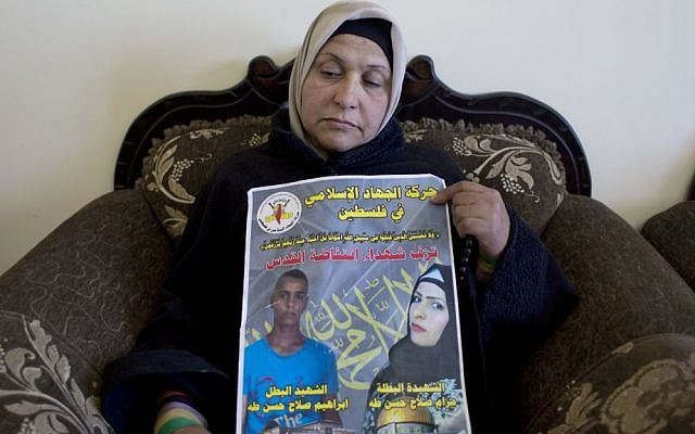 """Palestinian Fatema Taha, 40, the mother of Maram, 24 and Ibrahim Taha, 16, displays a poster with their pictures and Arabic that reads, """"Islamic Jihad in Palestine celebrates the martyrs of Jerusalem's uprising,"""" at the family house, in the West Bank village of Qatana, near Ramallah, Thursday, April 28, 2016. (AP Photo/Nasser Nasser)"""
