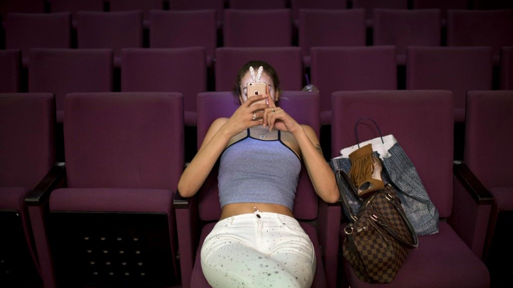 Madlen Matar, a contestant in the first Miss Trans Israel beauty pageant, uses her smartphone during rehearsal in Tel Aviv, Israel on Thursday, May 26, 2016. (AP Photo/Oded Balilty)