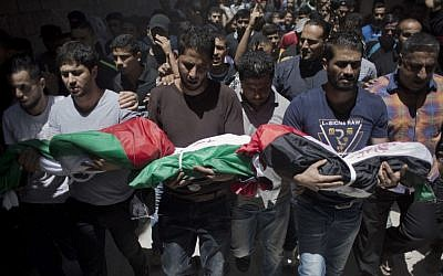 Palestinian mourners carry the bodies of three children who were killed in a fire caused by a candle, during their funeral in the Shati refugee camp in Gaza City, Saturday, May 7, 2016. (AP Photo/ Khalil Hamra)