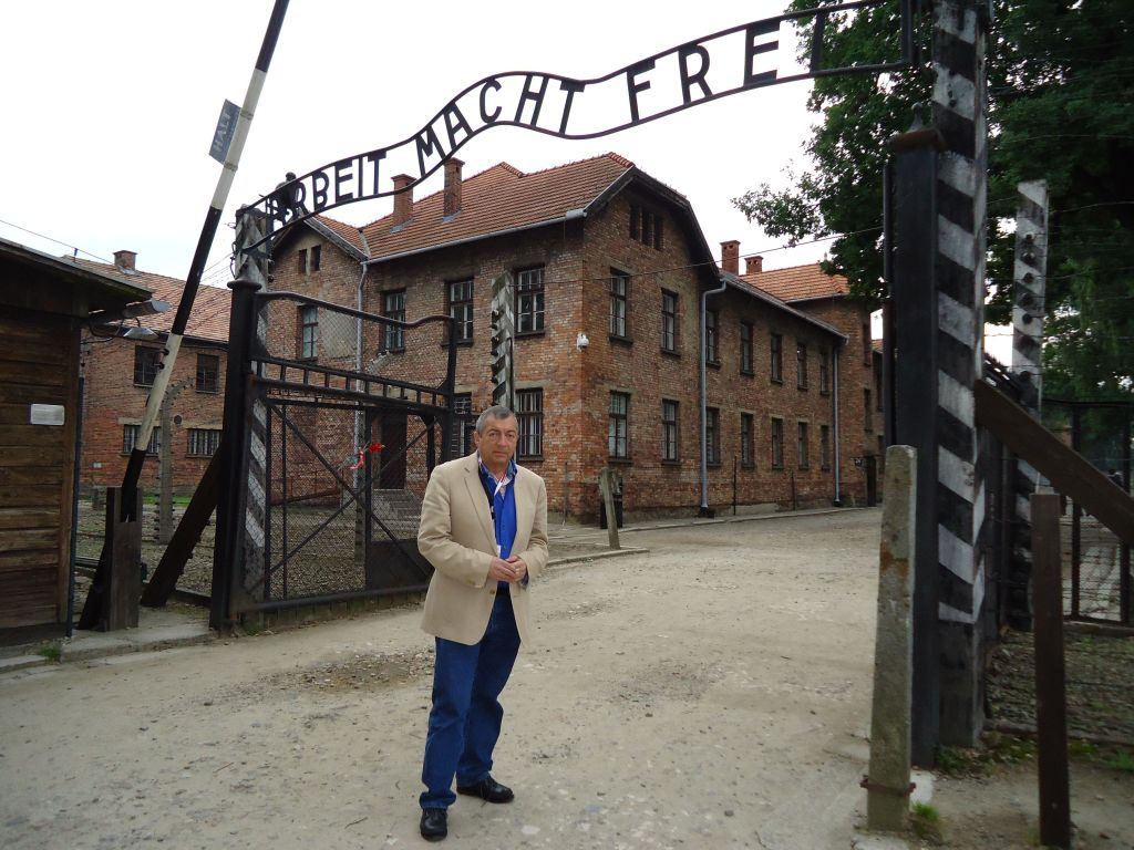 Filmmaker Philippe Mora beneath the infamous entrance to Auschwitz, 2011. The film 'Three Days in Auschwitz' is about three visits Mora made to the camp (courtesy)