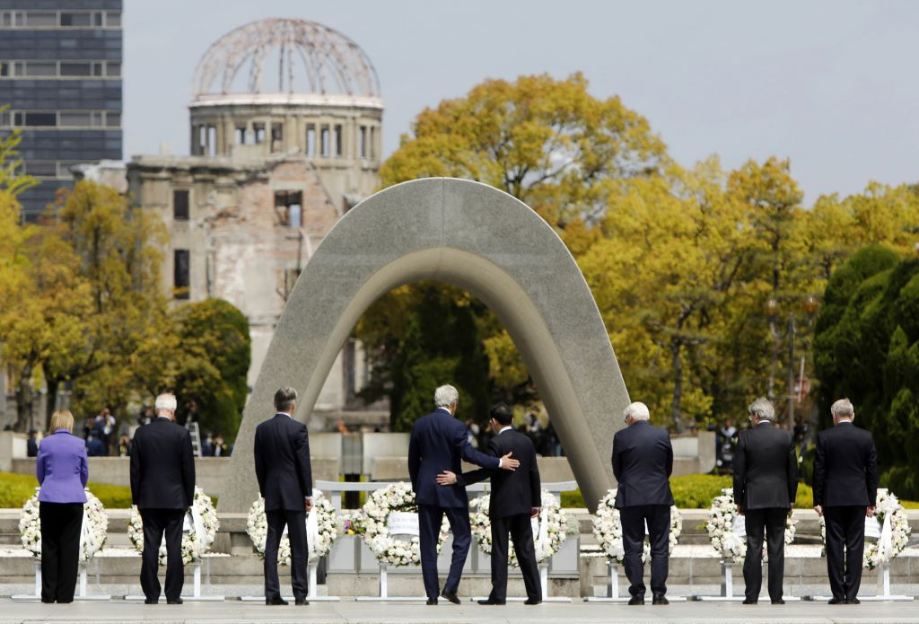 In this April 11, 2016, photo, U.S. Secretary of State John Kerry, fourth from left, puts his arm around Japanese Foreign Minister Fumio Kishida after they and fellow G7 foreign ministers laid wreaths at the cenotaph at Hiroshima Peace Memorial Park in Hiroshima, western Japan. (Jonathan Ernst/Pool Photo via AP, File)