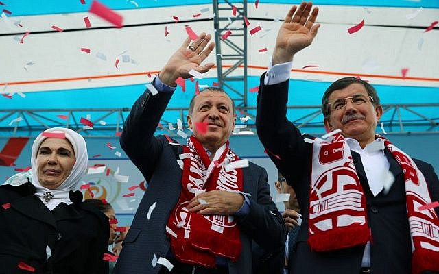 In this April 22, 2016 file photo, Turkey's President Recep Tayyip Erdogan, center, and Prime Minister Ahmet Davutoglu, right, salute together during a ceremony in Antalya, Turkey. (Yasmin Bulbul, Presidential Press Service, File, Pool via AP)