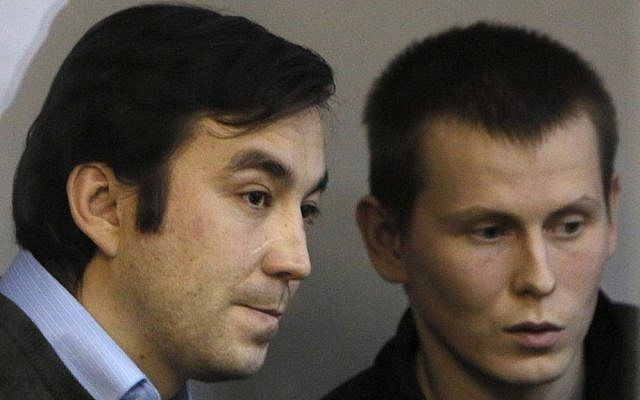 Russian soldiers, Capt. Yevgeny Yerofeyev, left, and Sgt. Alexander Alexandrov, captured while fighting in war-torn eastern Ukraine, sit in a cage during a trial hearing at the Holosiivskyi District Court in Kiev, Ukraine, January 12, 2016. (AP Photo/Sergei Chuzavkov, File)