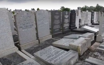 A view of the Blackley Jewish cemetery shows a line of headstones lying on the ground after being pushed over by vandals. (YouTube screenshot)