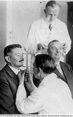 Otmar von Verschuer (rear) supervises the measurement of two men's head circumference as part of an anthropometric study of heredity. (Wikipedia)