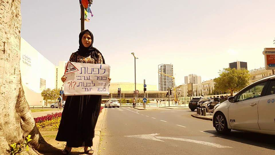"A Bedouin woman attending a protest for the village of Umm al-Hiran on May 20, 2016 stands on a street in central Tel Aviv with a sign that reads, ""Evacuating an Arab village in order to build a Jewish one?1?"" (Courtesy: Arab List Spokesperson)"
