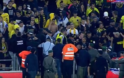 Fans of the Beitar Jerusalem soccer club fighting with police in the stands at Jerusalem's Teddy Stadium on May 1, 2016. (screen capture: YouTube/ONE)