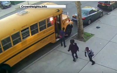 An image taken from security camera footage shows young men setting a bus  on fire in the Beis Rivkah elementary school in Crown Heights, Brooklyn, New York on April 8, 2016. (screen capture: YouTube)