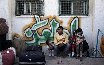 A Palestinian family sit next to their luggage as they wait for their turn to enter the Rafah border crossing with Egypt, in the southern Gaza Strip, May 11, 2016. (AP Photo/ Khalil Hamra)