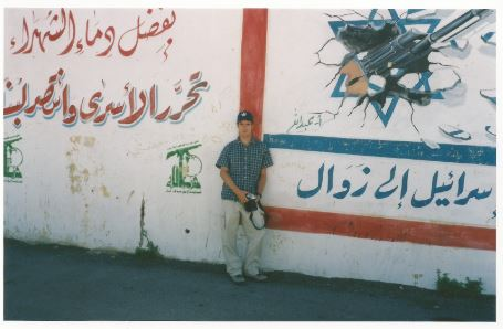 Matti Friedman, the tourist, in front of Hezbollah slogans in southern Lebanon (Courtesy Matti Friedman)