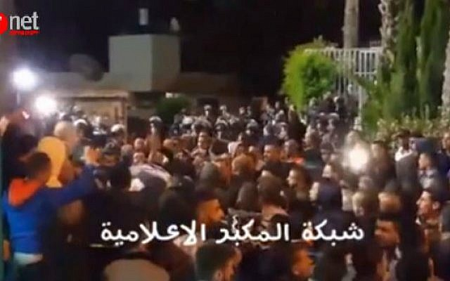 Demonstrators shout praise for terrorist Alaa Abu Jamal in the East Jerusalem neighborhood of Jabel Mukaber, outside the cemetery where he was being buried on May 23, 2016. (screen capture: Ynet)