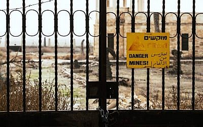 "A sealed gate preventing visitors from approaching a church at Qasr al-Yahud, the Jordan River site believed by many Christians to be the site of Jesus's baptism. A sign on the gate reads ""Danger mines!"" in Hebrew, Arabic and English. (YouTube screen capture)"