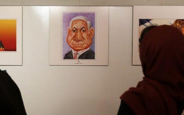 An Iranian woman looks at an anti-Israel cartoon of Prime Minister Benjamin Netanyahu at the second international exhibition of drawing and cartoons on the Holocaust in Tehran on May 14, 2016 (AFP PHOTO / ATTA KENARE)