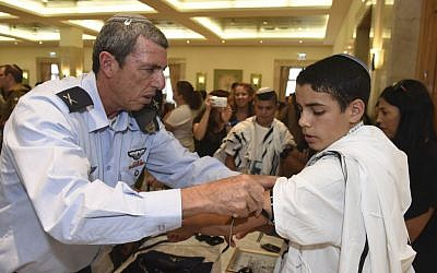 IDF Chief Rabbi Rafi Peretz teaches an IDF orphan how to put on tefilin for the first time at a Bar Mitzvah ceremony organized by the IDF Widows and Orphans Organization, in an undated photograph. (courtesy)